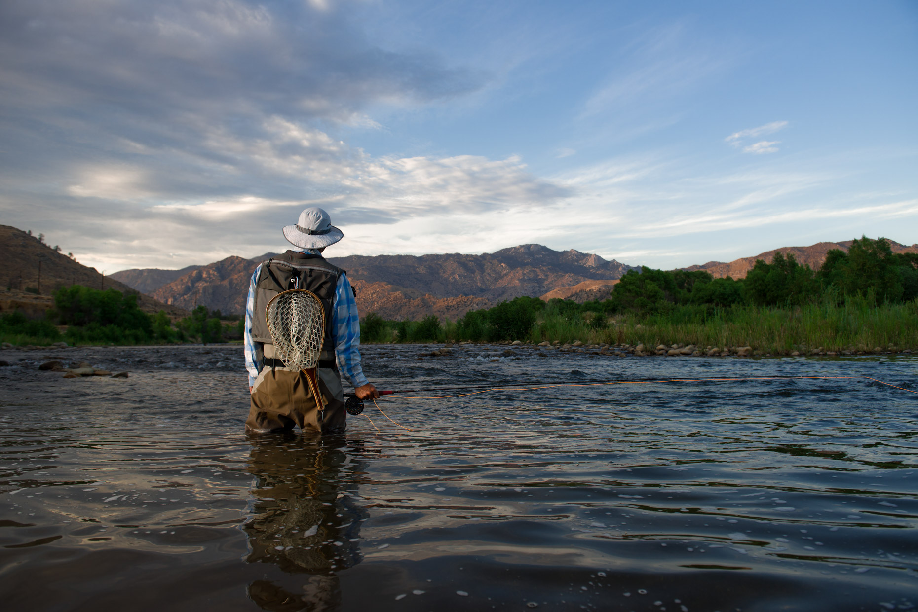 fly-fisherman-stands-with-back-to-camera-looking-upstream